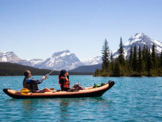 couple fishing from kayak on lake