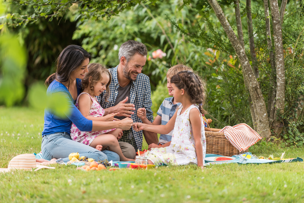 Cheerful family sitting on the grass during a picnic in a park